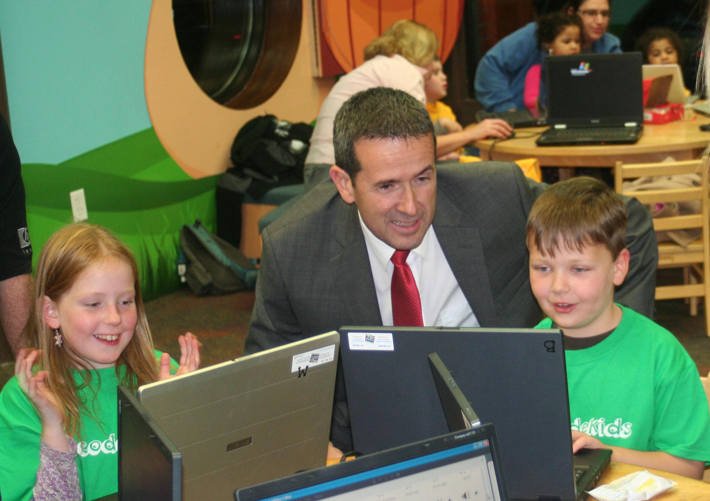Le ministre observe des enfants qui créent à l'aide de la technologie